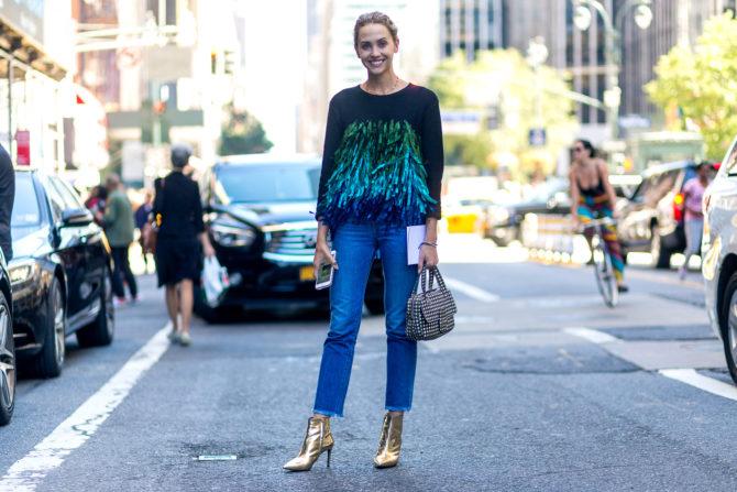 Девушка в чёрной кофте и синих джинсах на дороге