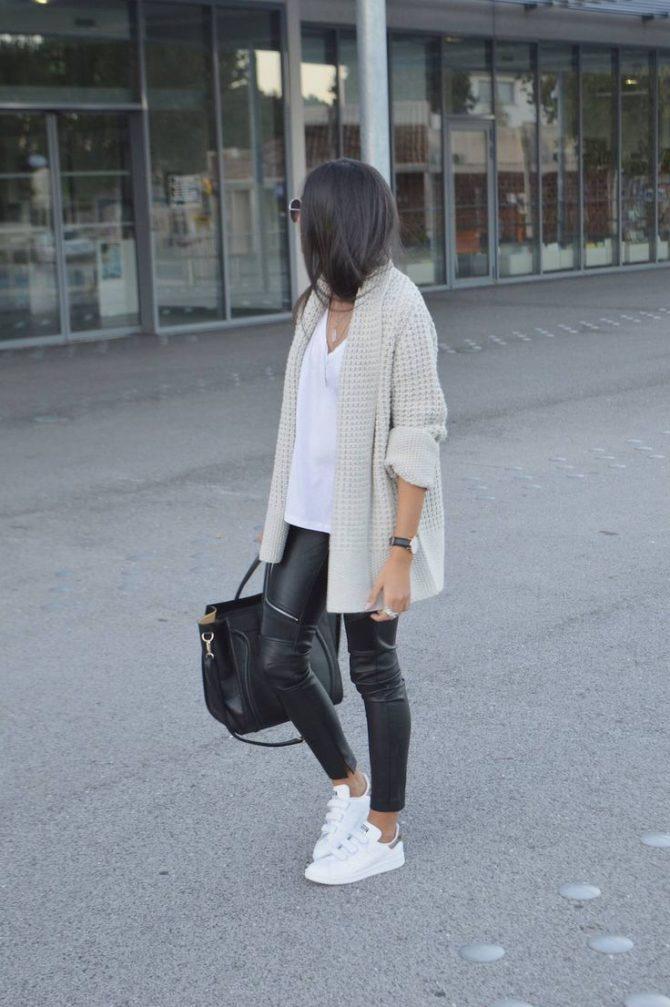 Девушка в кожаных брюках и кроссовках