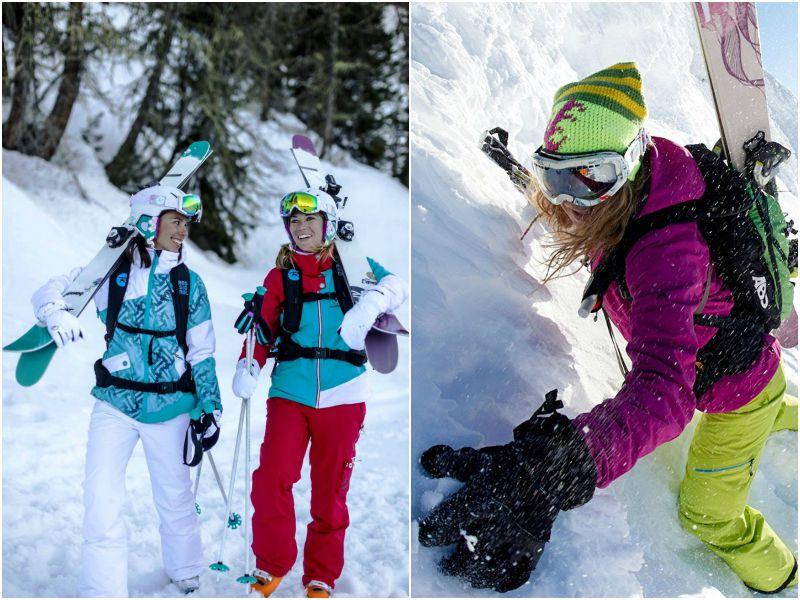 Девушки в горнолыжных костюмах с лыжами на плечах