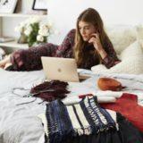 Вещи на кровати и девушка с ноутбуком