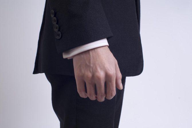 Рука мужчины на фоне пиджака крупным планом
