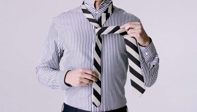 Мужчина завязывает галстук