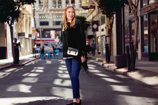 Девушка в джинсах и черном пончо на улице