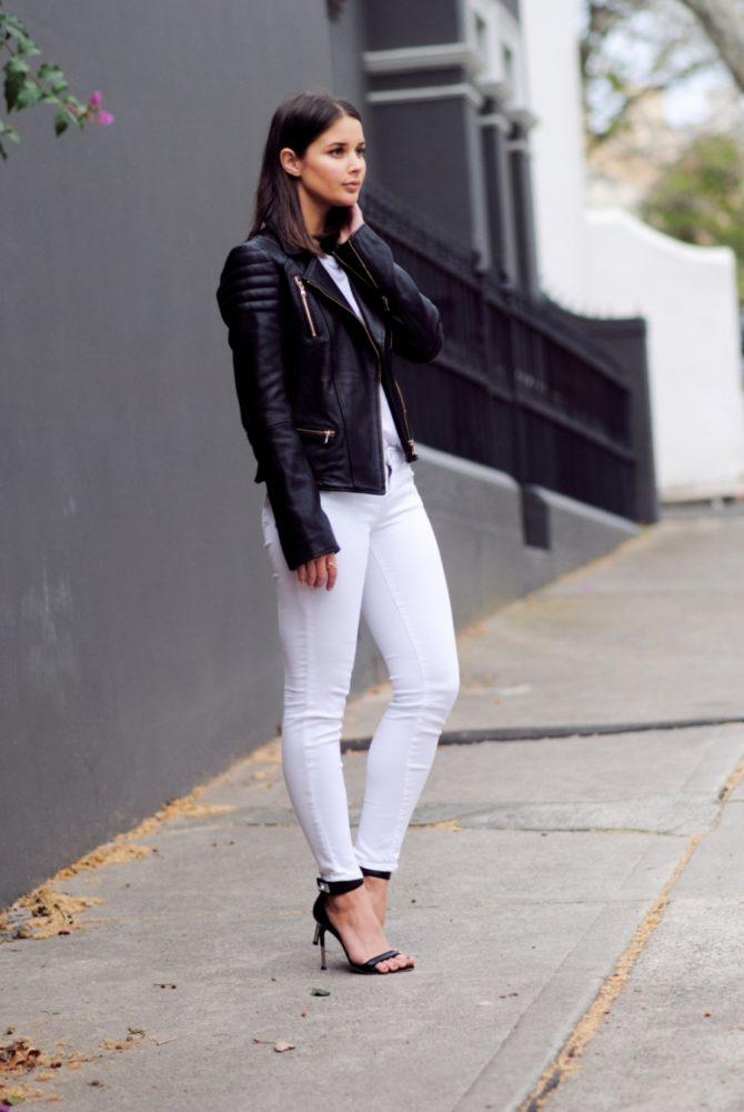Девушка в черной кожаной куртке и белых джинсах
