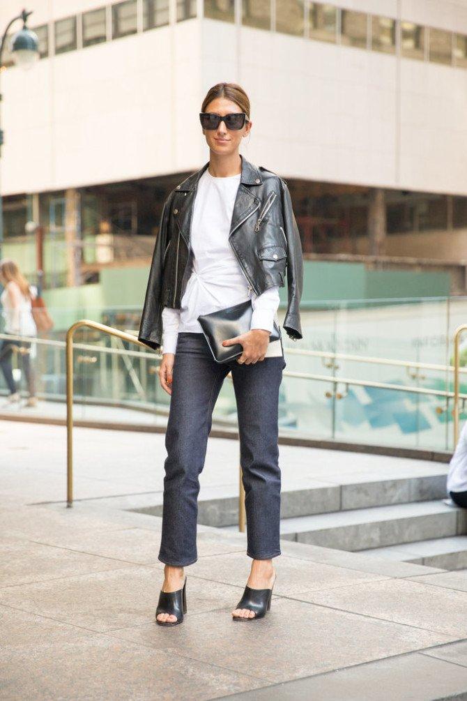 Девушка в джинсах и блузке с косухой поверх наряда