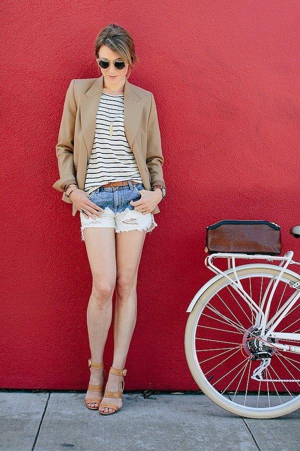 Девушка в джинсовых шортах у красной стены