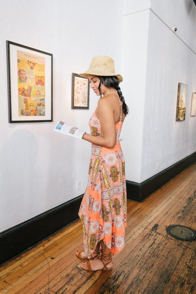 Девушка в ярком платьевозле картин