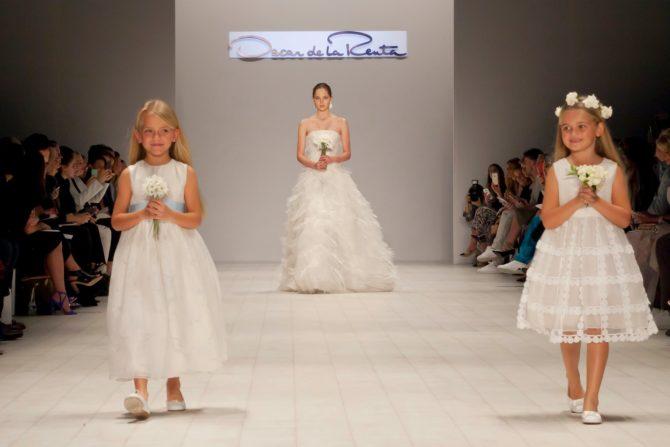 Модель в свадебном платьеи две девочки на подиуме