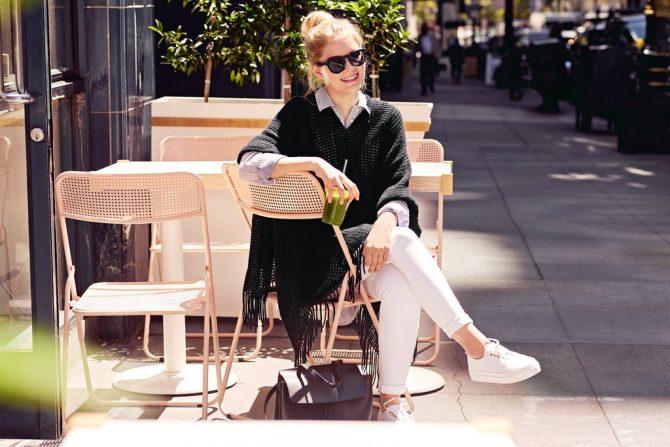 Девушка в черном пончо с белыми брюками и кроссовками